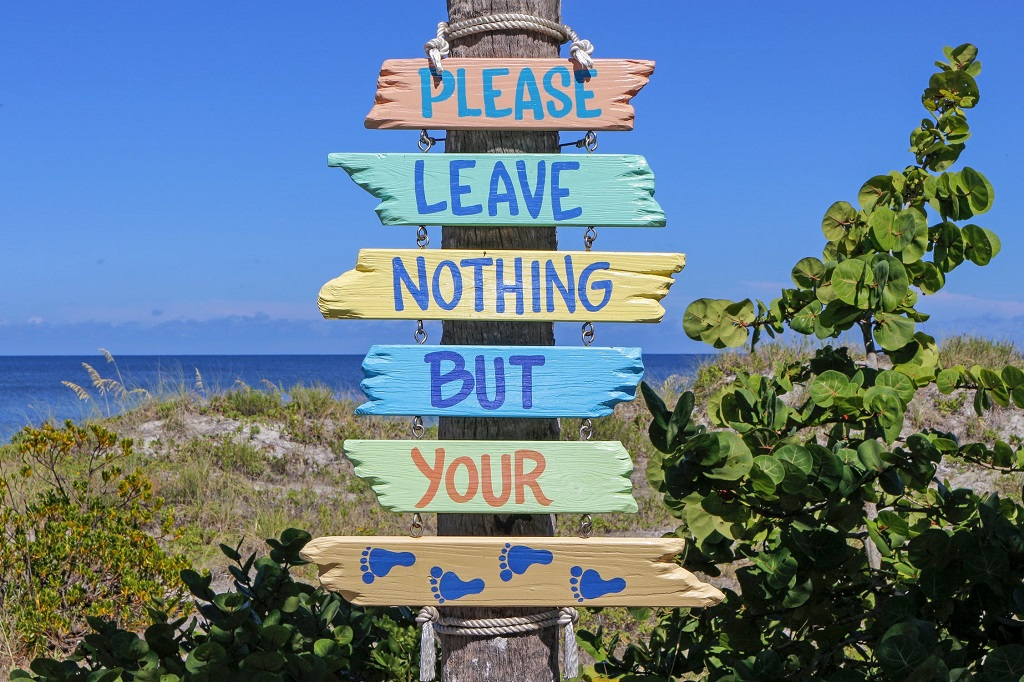 """Panorama spiaggia con messaggio """"please leave nothing but your prints"""""""